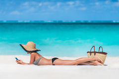 Setzen Sie Ferienfrau simsende sms unter Verwendung Telefon-APP auf den Strand Stockfotografie