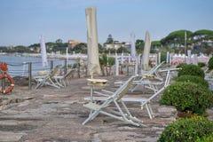 Setzen Sie früh morgens, Mangel an Leuten und gefaltete Regenschirme auf den Strand Lizenzfreie Stockfotografie