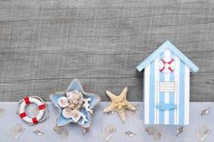Setzen Sie Hütte und Muscheln auf einem grauen hölzernen Hintergrund für Reise c auf den Strand stockfoto