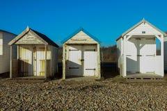 Setzen Sie Hütten an einem sonnigen Tag in Sussex auf den Strand Stockfotografie