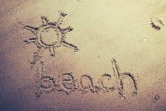 Setzen Sie handgeschriebenes im Sand des Strandes mit einer reizenden Sonne auf den Strand Stockfotografie