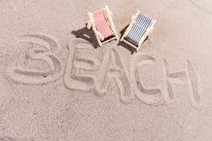 Setzen Sie Hintergrund, den Wortstrand auf den strand, der auf den Strand geschrieben wird Stockbilder
