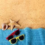 Setzen Sie Hintergrundgrenzsonnenbrille, -tuch, -Starfish und -meer auf den Strand Stockfotografie