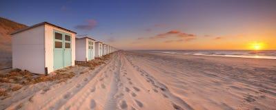 Setzen Sie Hütten bei Sonnenuntergang, Texel-Insel, die Niederlande auf den Strand Stockbild