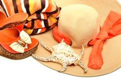 Setzen Sie Hut, Tuch, stilvolle Frauenschuhe und eine Muschel auf den Strand Lizenzfreie Stockfotografie