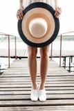 Setzen Sie Hutnahaufnahme in den Händen eines Mädchens auf einer Brücke auf den Strand Stockbilder