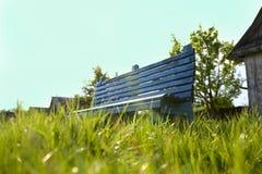 Setzen Sie im Garten auf die Bank, der durch grünes Gras umgeben wird Stockbilder