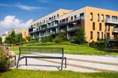 Setzen Sie im Park mit modernem Wohnblock im Hintergrund auf die Bank Stockfotos