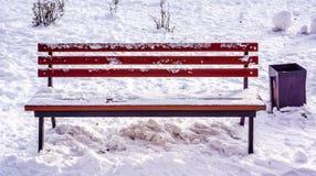 Setzen Sie im Winterstadtpark auf die bank, der mit Schnee mit schwarzem Korb nahe es aufgefüllt worden ist Lizenzfreie Stockbilder