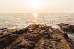 Setzen Sie in Indien am Sonnenuntergang, am Meer und an den Felsen auf den Strand Lizenzfreies Stockfoto