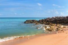 Setzen Sie Küstenlinie mit Steinen und Kiesel-, und azurblauemozean mit gelbem Sand auf den Strand lizenzfreie stockbilder