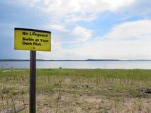 Setzen Sie, kein Leibwächter auf den Strand, schwimmen Sie auf eigene Gefahr Signage Stockfotografie