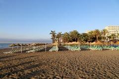 Setzen Sie Klubsessel und Strandschirm am einsamen sandigen Strand auf den Strand Costa del Sol (Küste des Sun), Màlaga in Andalu Lizenzfreies Stockfoto
