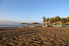 Setzen Sie Klubsessel und Strandschirm am einsamen sandigen Strand auf den Strand Costa del Sol (Küste des Sun), Màlaga in Andalu Stockfoto