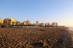 Setzen Sie Klubsessel und Strandschirm am einsamen sandigen Strand auf den Strand Costa del Sol (Küste des Sun), Màlaga in Andalu Lizenzfreie Stockfotos