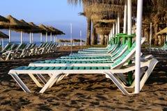 Setzen Sie Klubsessel und Strandschirm am einsamen sandigen Strand auf den Strand Costa del Sol (Küste des Sun), Màlaga in Andalu Lizenzfreies Stockbild