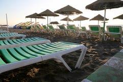 Setzen Sie Klubsessel und Strandschirm am einsamen sandigen Strand auf den Strand Costa del Sol (Küste des Sun), Màlaga in Andalu Lizenzfreie Stockfotografie
