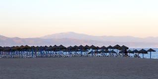 Setzen Sie Klubsessel und Strandschirm am einsamen sandigen Strand auf den Strand Costa del Sol (Küste des Sun), Màlaga in Andalu Stockfotografie