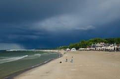 Setzen Sie in Kolobrzeg und in den drastischen schweren Wolken im Himmel auf den Strand Stockfotos