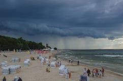 Setzen Sie in Kolobrzeg und in den drastischen schweren Wolken im Himmel auf den Strand Lizenzfreies Stockbild