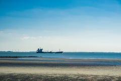 Setzen Sie Landschaft mit einem Bootssegeln auf Meer auf den Strand Lizenzfreies Stockbild