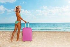 Setzen Sie Mädchen mit rosa Gepäck nahe dem Meer auf den Strand Lizenzfreie Stockfotos