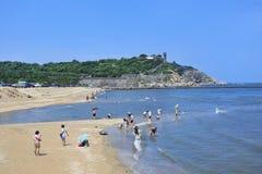 Setzen Sie mit einer alten Festung auf dem Hintergrund, Penglai, China auf den Strand Stockbilder
