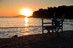 Setzen Sie mit kleinem Direktor wie Stuhl bei Sonnenuntergang in Sithonia auf den Strand Lizenzfreie Stockfotos