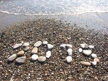 Setzen Sie mit Kos-guten Rutsch ins Neue Jahr 2015 Meer der Unschärfe blauem auf den Strand Stockbild