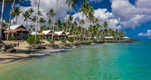 Setzen Sie mit mit KokosnussPalmen und Landhäusern auf Samoa-Insel auf den Strand stock footage
