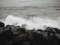 Setzen Sie mit schwarzem Sand mit Ozean mit großen schwarzen Steinen auf den Strand jpg lizenzfreie stockfotografie