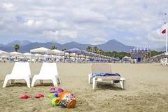 Setzen Sie mit Spielen für Kinder im Vordergrund auf den Strand Im backgrou stockfotografie