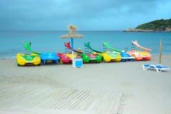 Setzen Sie mit Spielzeugwasserfahrzeugen an Sant-Ulme auf den Strand Lizenzfreie Stockfotografie