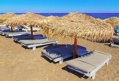 Setzen Sie mit Strohregenschirmen und hölzernen sunbeds auf Insel Satorini, Griechenland, Europa auf den Strand Lizenzfreie Stockbilder