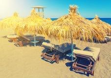 Setzen Sie mit Strohregenschirmen und hölzernen sunbeds auf Insel Satorini, Griechenland, Europa auf den Strand lizenzfreie stockfotos