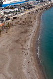 Setzen Sie mit Sunbathers, nahe dem Handelshafen auf den Strand Stockbilder