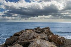 Setzen Sie mit Wasser in der Stille und in den Felsen auf den Strand Lizenzfreies Stockfoto