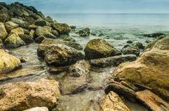 Setzen Sie mit Wasser in der Stille und in den Felsen auf den Strand Stockbild