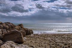 Setzen Sie mit Wasser in der Stille und in den Felsen auf den Strand Stockfotografie