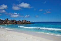Setzen Sie mit weißem Sand, blauem Ozean und Steinen, Seychellen auf den Strand Stockfoto