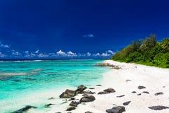 Setzen Sie mit weißem Sand und schwarzen Felsen auf Rarotonga, Koch Islands auf den Strand Lizenzfreie Stockfotografie