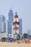 Setzen Sie mit Wolkenkratzern auf dem Hintergrund, Yantai, China auf den Strand Stockbild