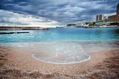 Setzen Sie in Monaco an einem stürmischen Tag mit dunklen Wolken auf den Strand Und azurblaues Meer mit gelbem Sand Stockfotos