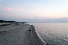 Setzen Sie nach dem Sonnenuntergang mit Sand und Wolken auf den Strand Lizenzfreies Stockfoto
