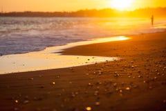 Setzen Sie Nahaufnahme in den Strahlen der untergehenden Sonne auf den Strand Stockbild