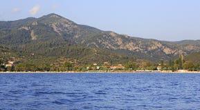 Setzen Sie in Neos Marmaras und Berge von Sithonia auf den Strand Lizenzfreie Stockbilder