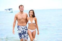 Setzen Sie Paare beim Liebesgehen glücklich im Wasser auf den Strand Lizenzfreie Stockfotos