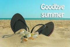 Setzen Sie Pantoffel auf dem Sand mit den Oberteilen und den Wörtern des Sommers Auf Wiedersehen vor dem hintergrund des Strandes Lizenzfreies Stockfoto