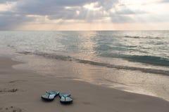 Setzen Sie Pantoffel auf dem Sand in Sonnenuntergang und Meer auf den Strand Stockfotografie
