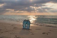 Setzen Sie Pantoffel auf dem Sand in Sonnenuntergang und Meer auf den Strand Stockbild